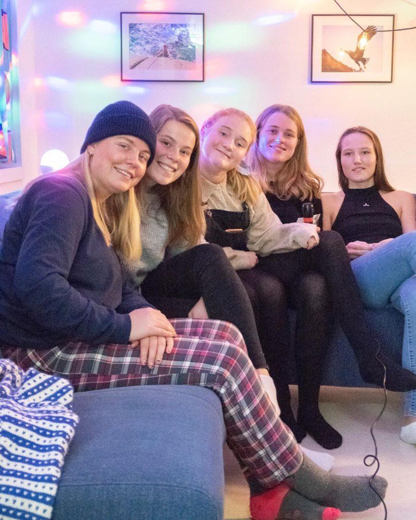 Elever i koseklær sitter i sofa