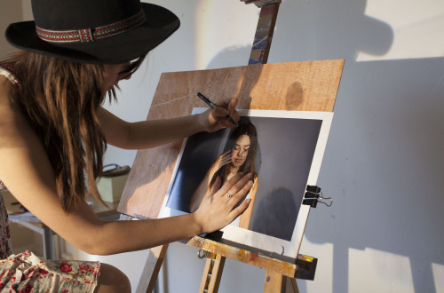 Jente som holder på med et bilde på et staffeli