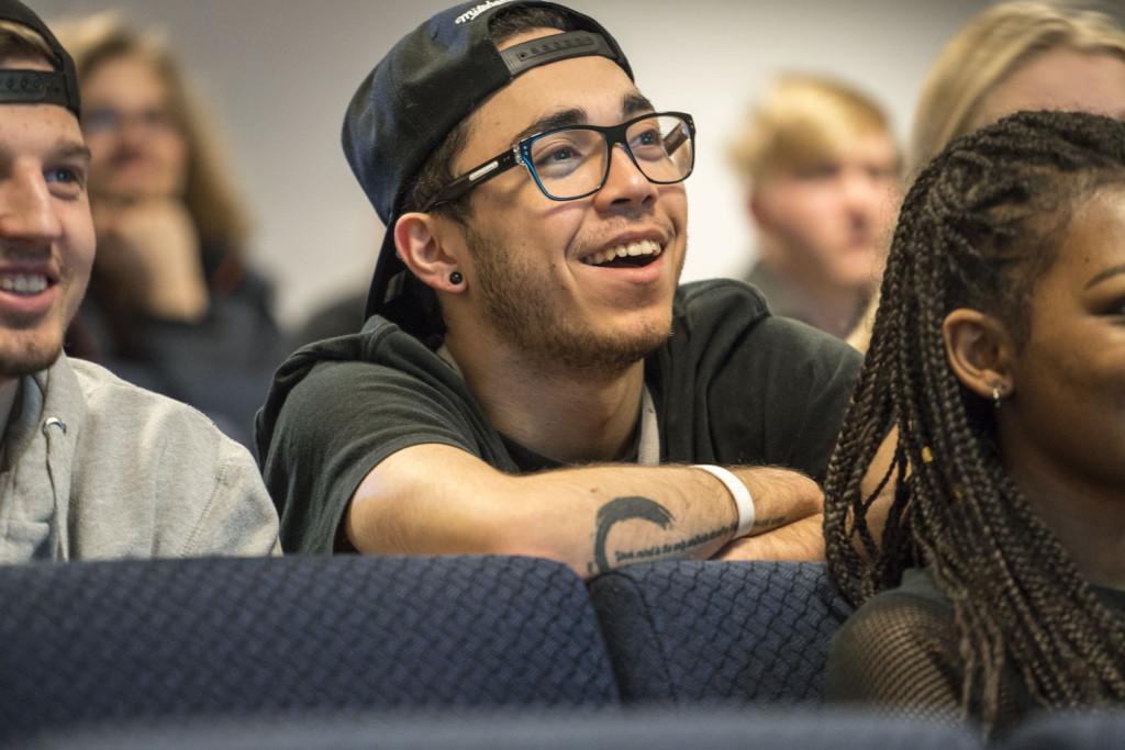Bilde av smilende gutt i auditorium