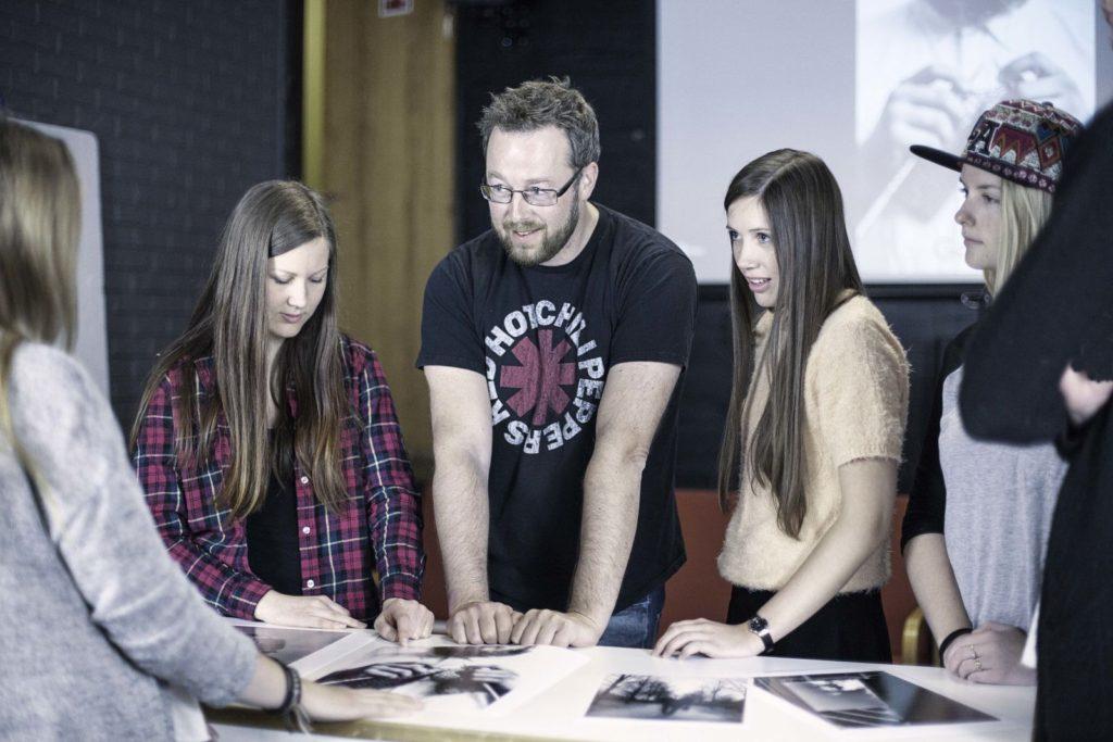 Bilde av elever og lærer rundt et bord.