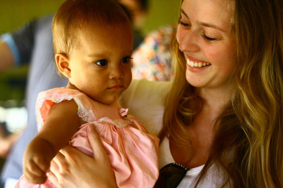 Ung jente smiler og holder ei lita jente i armene