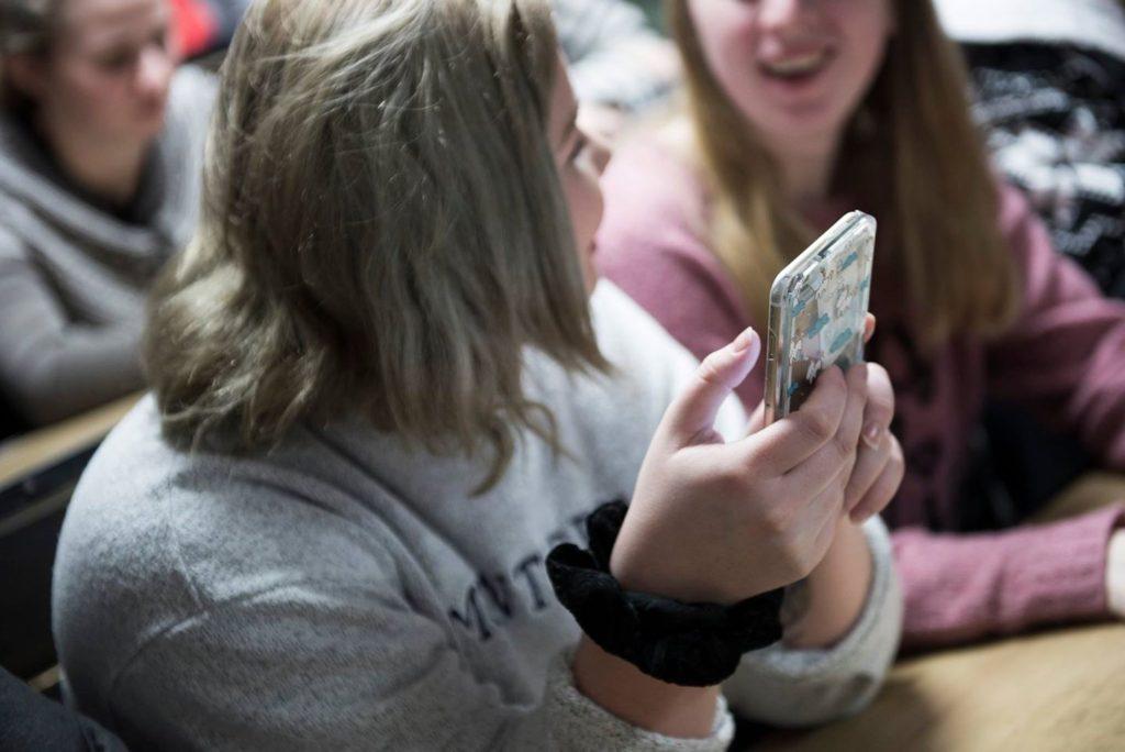Jente med smarttelefon i hendene.