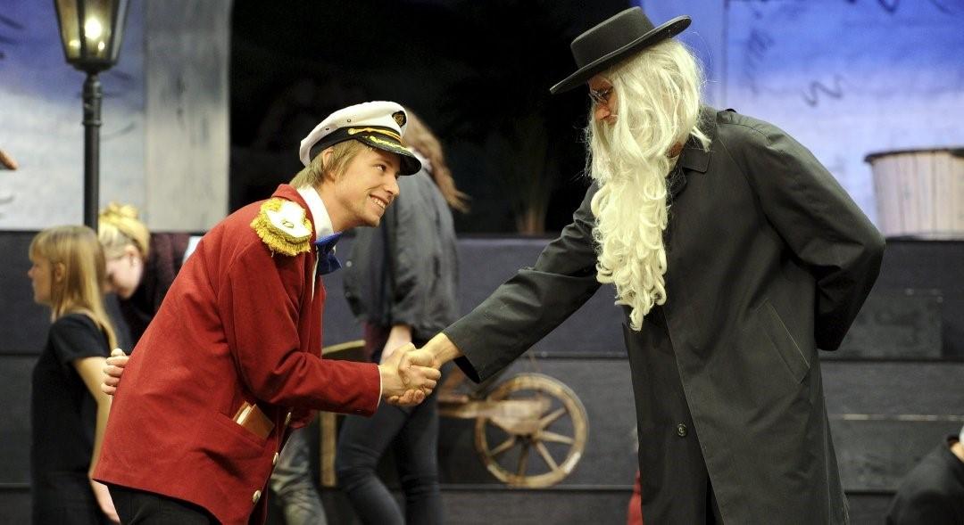 To unge menn i kostyme spiller teater og håndhilser.