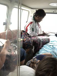 Ylva ligger i sykebilen og blir passet på av en representant fra Toten folkehøgskole og en lokal sykepleier. Bildet er tatt gjennom luken fra forsetet i bilen.