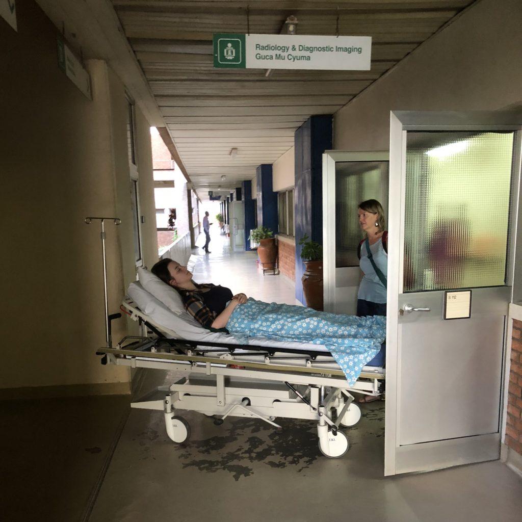 King Faisal sykehuset i Kigali var et stort og moderne sykehus der Ylva fikk god behandling. Her er hun på vei inn for å ta røngtenbilder av kneet. Ved siden av står Marianne, som jobbet for Toten folkehøgskole og fulgte Ylva på sykehuset.