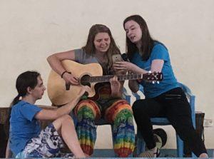 Med en stol og sitte på så klarte Ylva også å opptre på scenen på jenteskolen i Kampala. Her med medelevene Matilde Vadseth Furholm og Sasha Unruh