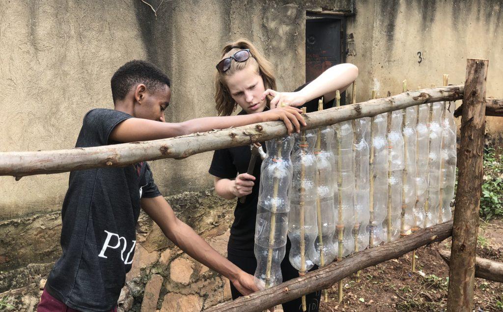En elev fra Toten folkehøgskole og en fra EcoAction jobbet sammen om å bygge et gjerde av gamle flasker