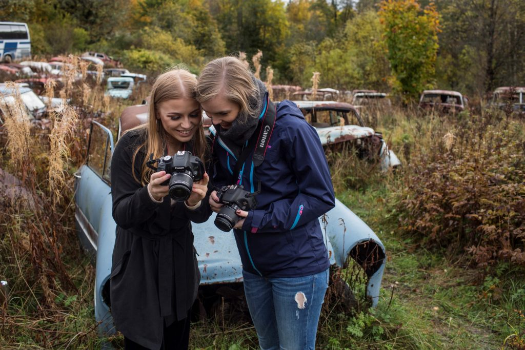 To jenter med fotoappart foran et bilvrak.
