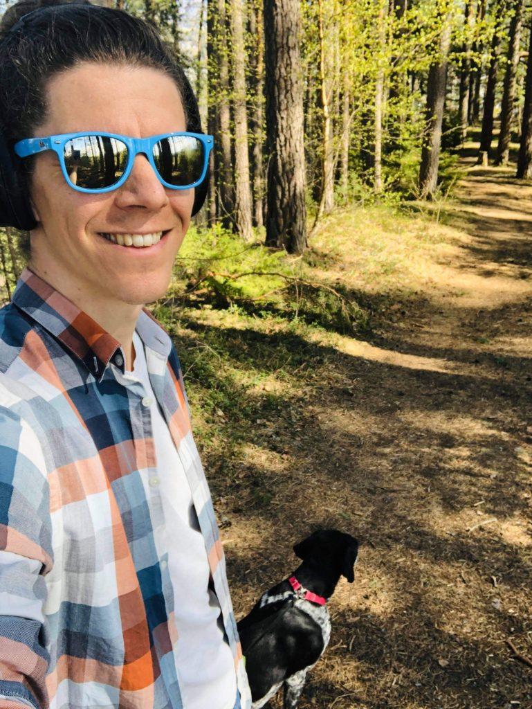 Mann går på tur i skogen med headset og hund.