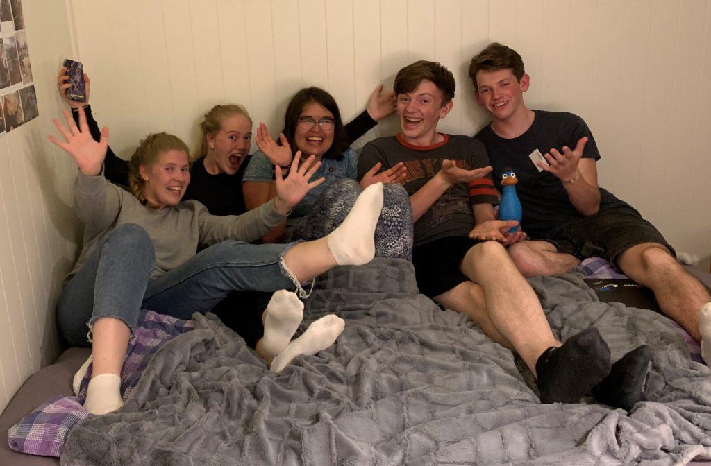 Seks elever sitter på en seng.