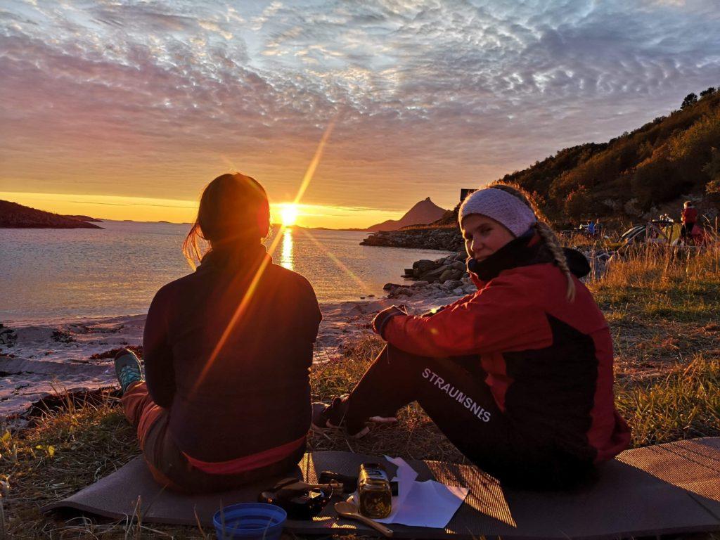 solnedgang, to personer sittende i fjæra