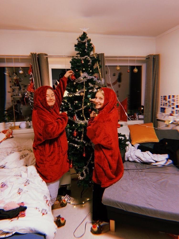 To jenter i røde gensere pynter et juletre på rommet sitt.