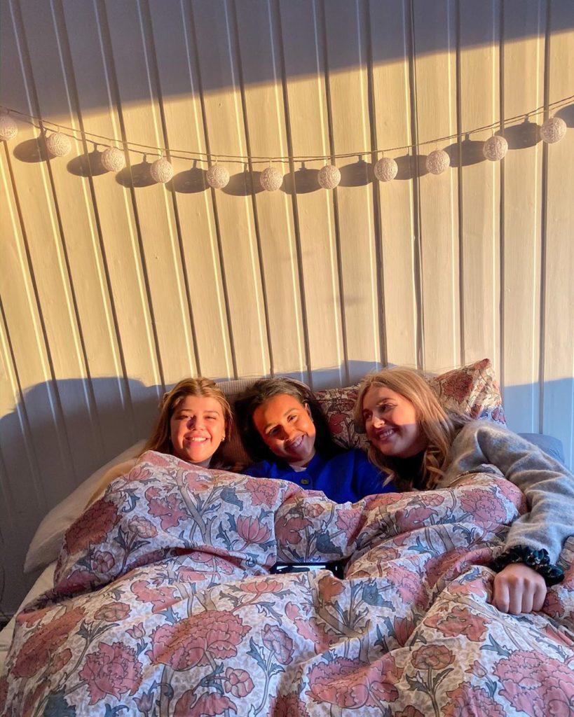 Tre elever ligger under dyna i en seng. På veggen bak henger ei lyslenke.