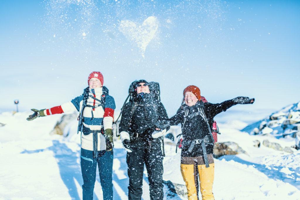 Elever på tur om vinteren. De kastar snø i været og et hjerte synes på himmelen.