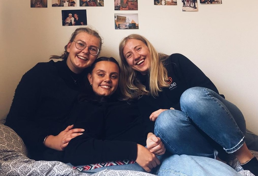 Tre jenter sitter på ei seng på et folkehøgskolerom.