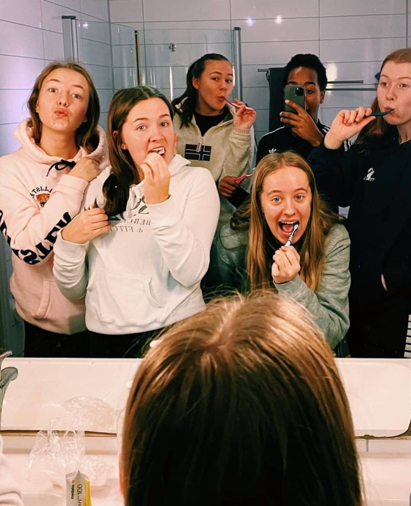 Kvinnelige elever pusser tenna sammen. Bildet er tatt i et speil.