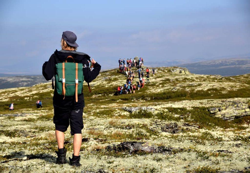 Elev med ryggen til og rygsekk går på fjelltur.