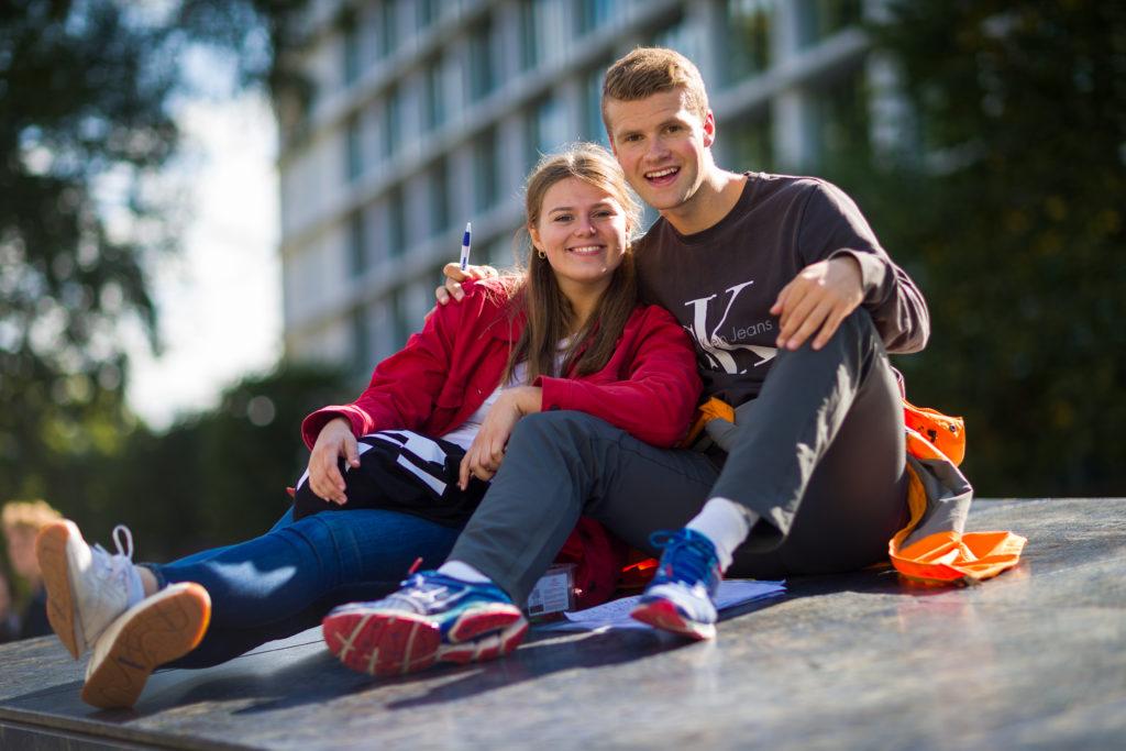 En kvinnelig og en mannlig elev sitter sammen utendlrøs.