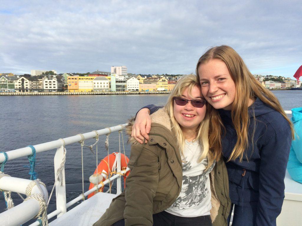 To elever sitter på en båt og holder rundt hverandre mens de smiler til kamera.