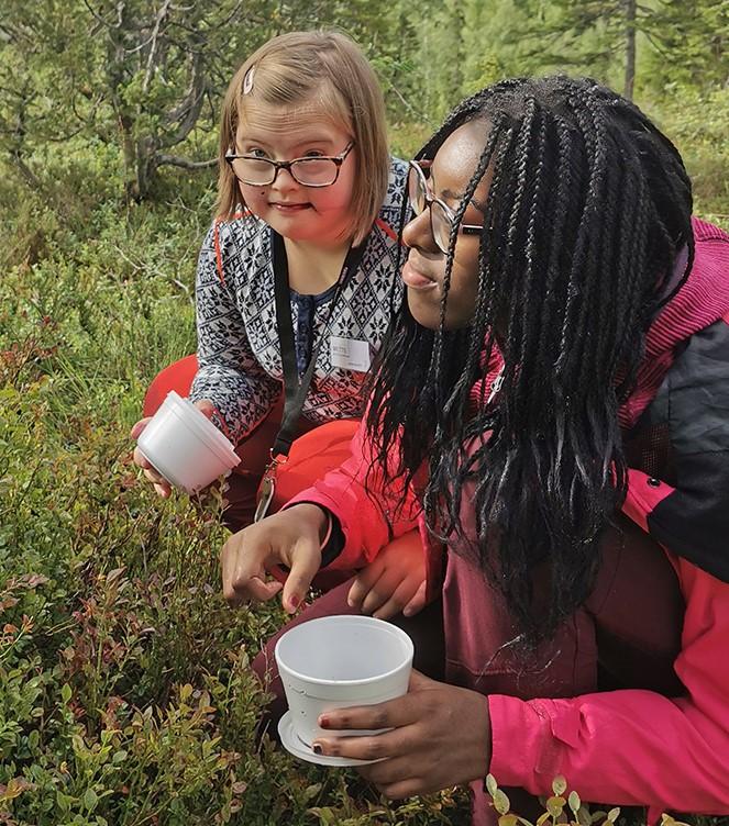 To elever plukker bær i skogen.